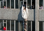 Woman in wedding gown is grabbed by local community officer, as she attempts to kill herself by jumping out of seven-storey residential building in Changchun