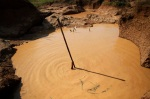 A man holds a stick as he installs a pump to extract mud at a primitive gold mine in Panompa near Phichin